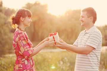 Man giving to his woman a gift box. Retro style.