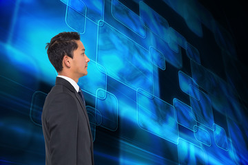 Composite image of serious young asian businessman