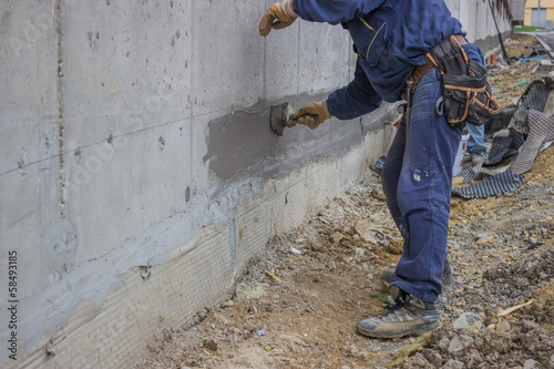 Construction workers with brush applied hydro insulation