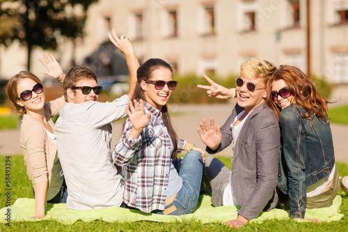 group of students or teenagers waving hands