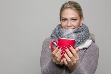 Roter Becher in Händen gehalten von Frau der kalt ist