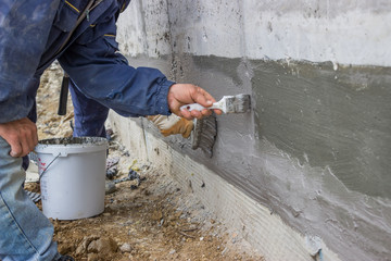 Construction workers with brush applied hydro insulation 2