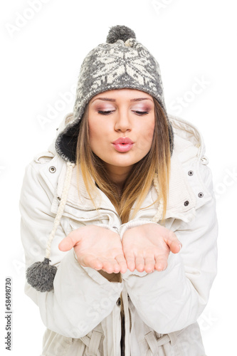Cute girl blowing kiss or snowflakes