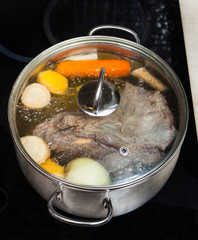 boiling of beef broth with seasoning vegetables