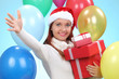 happy girl in red Santa hat holding gift box