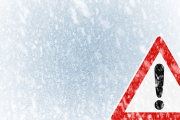 Snow on an ice covered windshield with warning sign