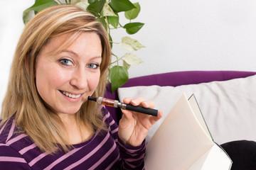 Frau auf Sofa mit elektrischer Zigarette und Buch