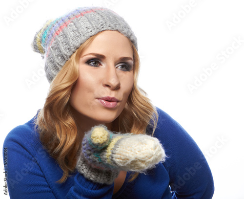Woman blowing a winter kiss