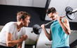 Постер, плакат: Young man motivating gym buddy during bicep exercise