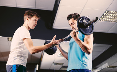 Young men training in gym weight training
