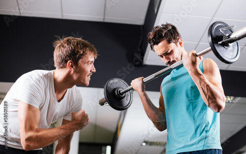 Young man motivating gym buddy during bicep exercise