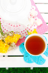 Beautiful set with tea on wooden picnic table close-up