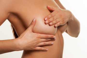 Naked woman checking fro breast cancer