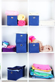 Blue textile boxes with towels and clothes in white shelves