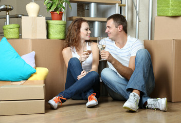 Young couple celebrating moving to new home sitting among boxes