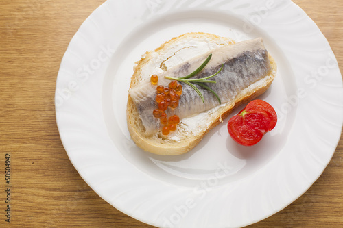 Sandwich with herring fish and caviar on bread, cherry tomato