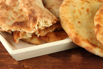 Pita breads on tray on table close up