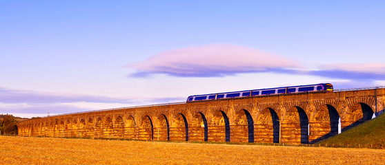 Old masonry arched viaduct carrying a train