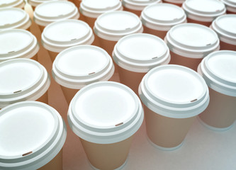 A row of paper coffee cups on a white background.