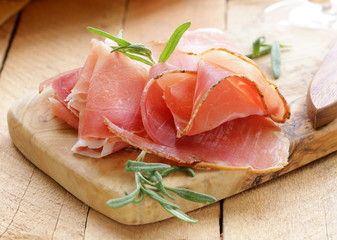 parma ham (jamon) sliced ​​on a wooden board