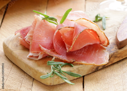 parma ham (jamon) sliced ​​on a wooden board - 58509933