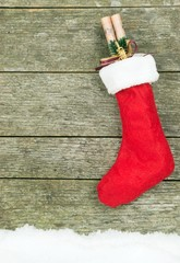 A Christmas stocking hanging on a wooden background