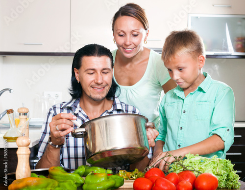 Happy family of three cooking vegetables