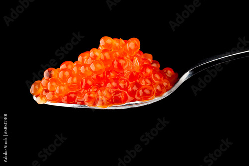 Red caviar in metal teaspoon isolated on black