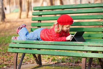 little girl working with tablet pc in the park.