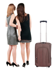 Two businesswoman traveling with suitcas and  looking at wall.