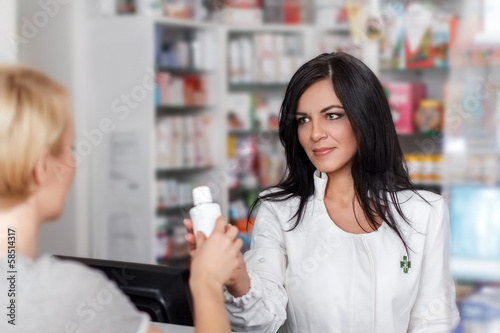 Pharmacist selling medicine in drugstore