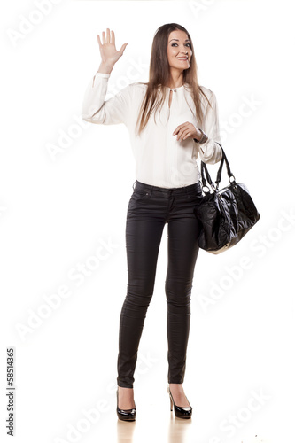 Smiling young business woman waving hand on white