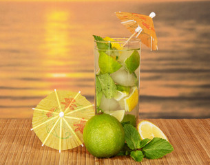 Mojito with umbrellas against sea sunset