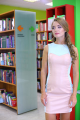 beautiful woman stands near the shelf with books