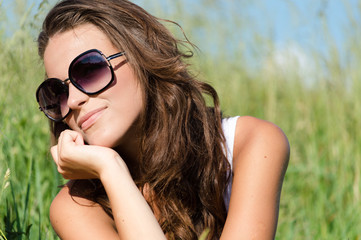 Beautiful young woman wearing sun glasses on summer day