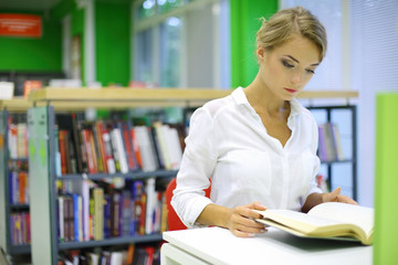 woman reading book in the reading room of library