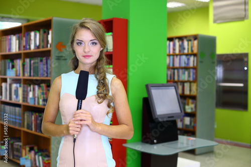 woman with a microphone in hand in the library