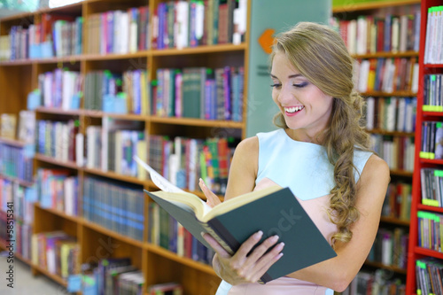 woman is looking joyfully into a book among bookshelves