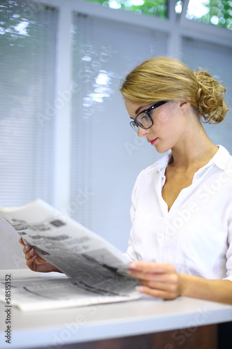 girl with glasses reading a newspaper at table