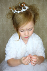 A little girl in crown looks at the rhinestones