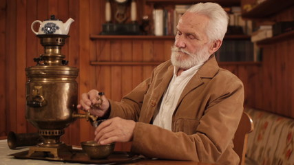white haired old man drinking tea from a samovar self boiler