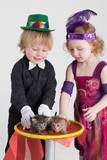 Two children in costumes magicians and two kittens