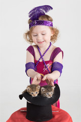 Little girl in costume magician pulls out kittens