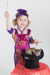 girl in costume magician waves her wand over cylinder