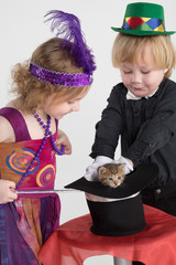 children in costumes magician take out kitten from the cylinder
