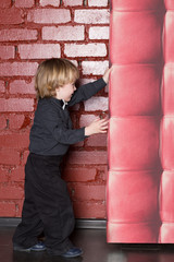 Little boy on a background of a brick wall