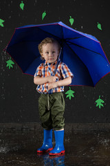 Little boy with blue umbrella on background of black wall with l