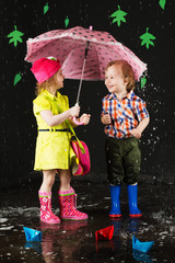 Little girl and boy hiding from the water under umbrella