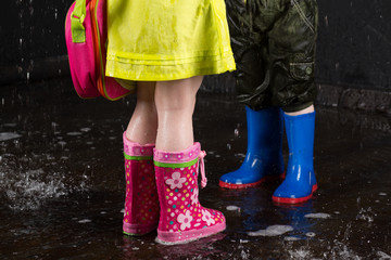 Childrens legs wearing in colorful rubber boots in water