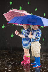 Little girl and boy in a striped vest under umbrellas